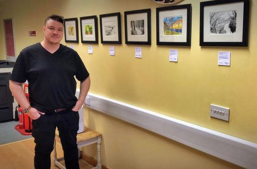 Artist Chris Richards standing in front of his framed artwork